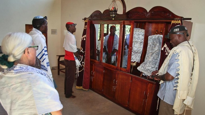 In this photo taken Thursday, Nov. 3, 2016, Muriel Hackel from Boston, left, and Ugandan Seth Yonadav, right, who serves as cantor, join other Ugandan Jews to pray in front of the Torah Ark, at the new Stern Synagogue in Mbale, eastern Uganda. The synagogue, built largely with money donated by Americans, is a source of pride for hundreds of Ugandan Jews known locally as the Abayudaya, who have tenaciously maintained their belief despite the prejudice they have suffered over the years in this Christian-dominated country. (AP Photo/Stephen Wandera)