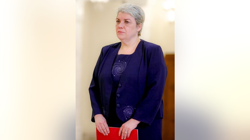 In this photo taken May 20, 2015, Sevil Shhaideh, 52, stands at the Romanian presidency before being sworn in as regional development minister in Bucharest, Romania. Liviu Dragnea, chairman of Romania's Social Democratic party which won the parliamentary election, proposed Wednesday that Sevil Shhaideh take the post of prime minister. (AP Photo/Octav Ganea)