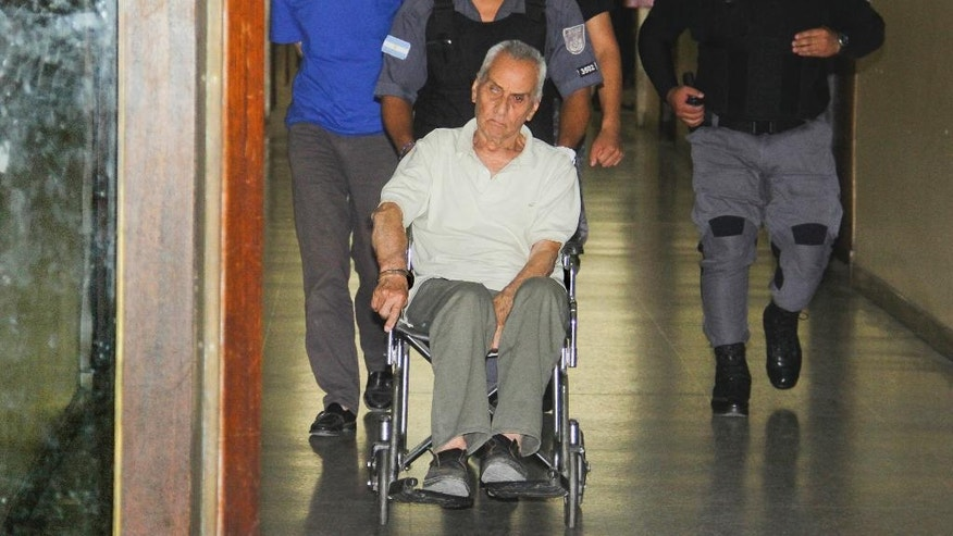 Handcuffed to a wheelchair, priest Nicola Corradi and the Rev. Horacio Corbacho, left, are escorted to a courtroom in Mendoza, Argentina, Thursday, Dec. 22, 2016. In late November, police arrested Corradi and Corbacho, after several students came forward with shocking childhood tales of the sexual abuse suffered over years at a school for hearing impaired children, in remote northwestern Argentina. (AP Photo/Emmanuel Rodriguez Villegas)