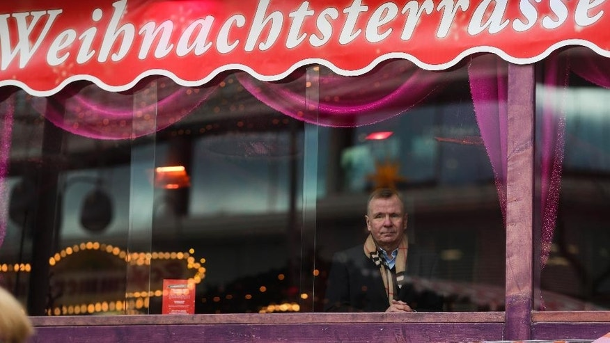 Eye witness Axel Kaiser poses for a photo at the window of his restaurant at the reopened Christmas market, three days after a truck ran into the crowd and killed several people, at the Kaiser Wilhelm Memorial Church in Berlin, Thursday, Dec. 22, 2016. The restaurant's name is 'Christmas Terrace'. (AP Photo/Markus Schreiber)