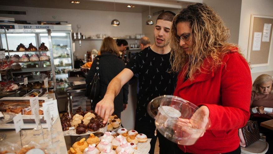 A bakery employee helps a customer choose doughnuts at a shop in Israel.