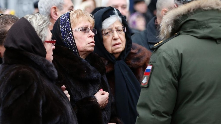 Marina Karlova, second left, a widow of killed Russian ambassador to Turkey, Andrei Karlov, and his mother Maria, third left, stand outside the Foreign Ministry headquarters in Moscow, Russia, Thursday, Dec. 22, 2016. Karlov was fatally shot by a Turkish policeman Monday in a gathering in Ankara, Turkey. (Sergei Ilnitsky/Pool photo via AP)