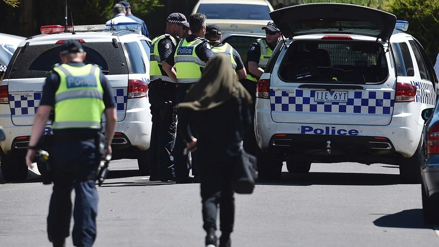 Dec. 23, 2016: Police accompany a woman as they attend the scene where a house was raided at Meadow Heights in Melbourne, Australia.