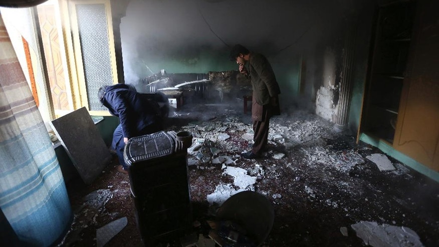Afghan men inspect the remains of their belongings at a parliament member's house in the aftermath of gunmen attack at last night in western Kabul, Afghanistan, Thursday, Dec. 22, 2016. (AP Photo/ Rahmat Gul)