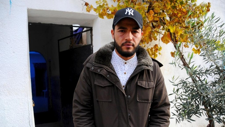 "The brother of fugitive Tunisian extremist suspected in Berlin's deadly Christmas market attack, Abdelkader Amri, poses for a photo in front of the family house where Anis Amri used to live, in Oueslatia, central Tunisia, Thursday, Dec. 22, 2016. Brother Abdelkader Amri told The Associated Press, ""I ask him to turn himself into the police. If it is proved that he is involved, we dissociate ourselves from it."" (AP Photo/Riadh Dridi)"