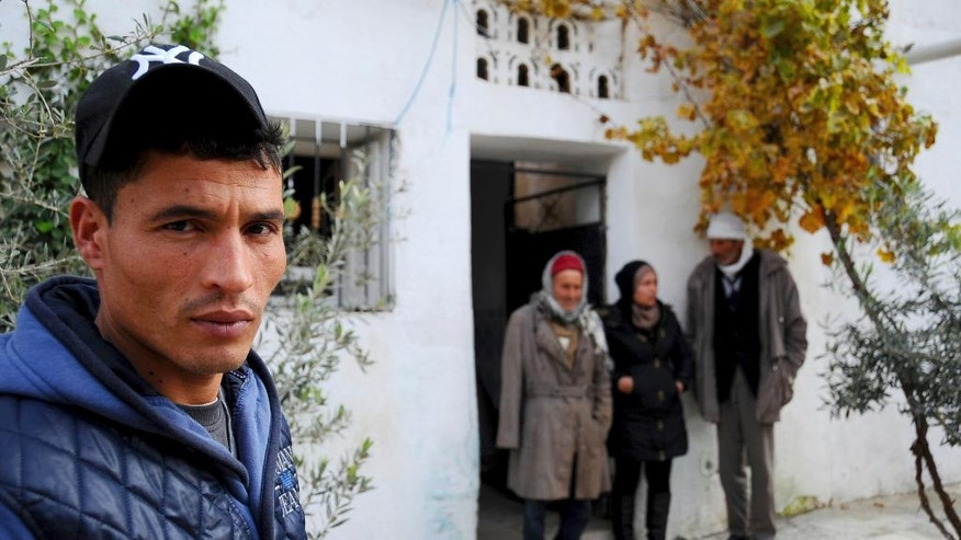 The brother of fugitive Tunisian extremist suspected in Berlin's deadly Christmas market attack, Walid Amri , poses for a photo in front of the family house where Anis Amri used to live, in Oueslatia, central Tunisia, Thursday, Dec. 22, 2016. Amri's family members, speaking from his hometown, were shaken to learn he's the prime suspect in Monday's rampage, which killed 12. (AP Photo/Riadh Dridi)