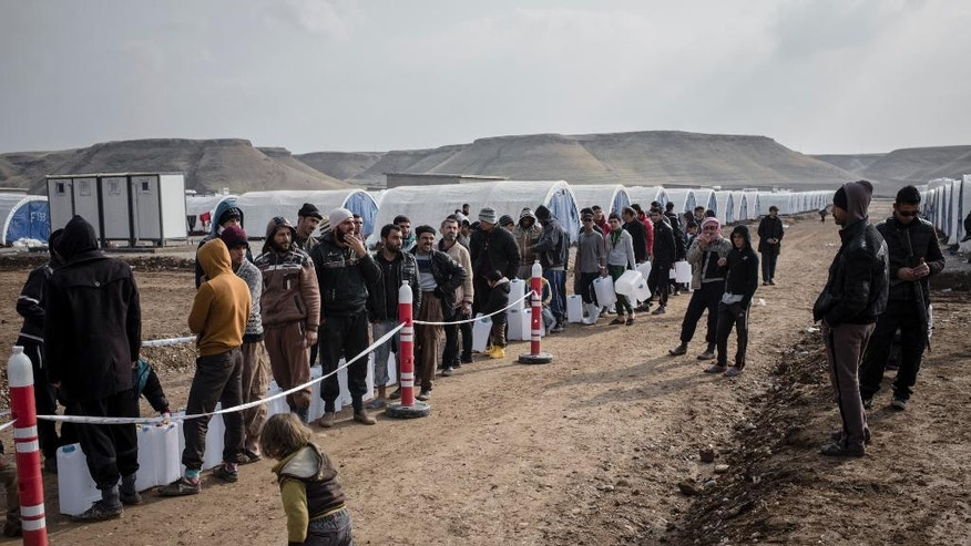 Men wait in line for fuel distributions at Sewdinan Camp for the displaced near Khazer, Iraq on Wednesday, Dec. 21, 2016. Human Rights Watch said Wednesday that Islamic State fighters are deliberately targeting civilians who refuse to join them as they retreat ahead of the advancing Iraqi forces. In a statement, it said at least 19 civilians were killed and dozens wounded in the period from the third week of November into the first week of December. (AP Photo/Cengiz Yar)