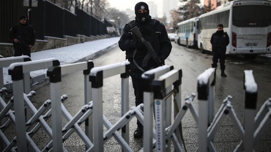 A Turkish police officer secures the road leading to the Russian embassy in Ankara, Turkey, Wednesday, Dec, 21, 2016. Russian Ambassador to Turkey, Andrei Karlov, was assassinated Monday by a police officer during the opening of a photo exhibition. (AP Photo/Emrah Gurel)