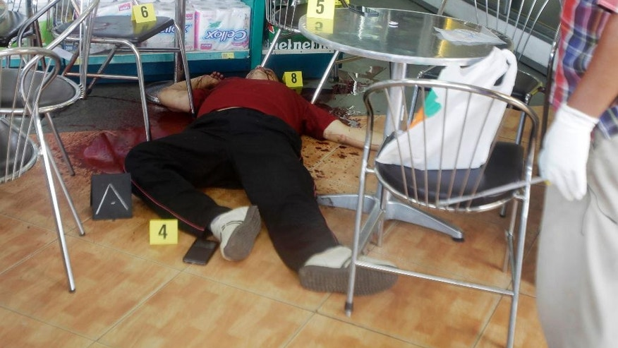 FILE - In this July 10, 2016, file photo, the body of Kem Ley, a prominent Cambodian political analyst, lays on the floor with evidence markers after he was shot inside a shop in Phnom Penh, Cambodia. Kem Ley, a poor rice farmer's son turned champion of Cambodia's have-nots, was sipping his usual iced latte in the same chair he had occupied most mornings for years when a former solider he may never have met walked into the Caltex gas station cafe. Armed with a semi-automatic Glock pistol, the assassin fired into his chest and head, execution-style. Then he walked casually away from the scene. (AP Photo/Heng Sinith, File)