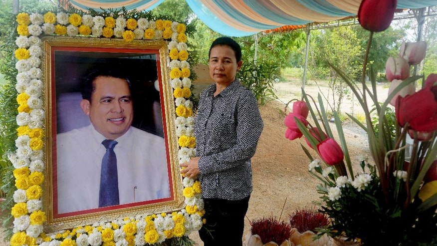 In this Nov. 20, 2016 photo, Kem Thavy stands by a portrait of her brother Kem Ley at his grave in Ang Takok, Cambodia. Kem Ley, a poor rice farmer's son turned champion of Cambodia's have-nots, was sipping his usual iced latte in the same chair he had occupied most mornings for years when a former solider he may never have met walked into the Caltex gas station cafe. Armed with a semi-automatic Glock pistol, the assassin fired into his chest and head, execution-style. Then he walked casually away from the scene. (AP Photo/Denis Gray)