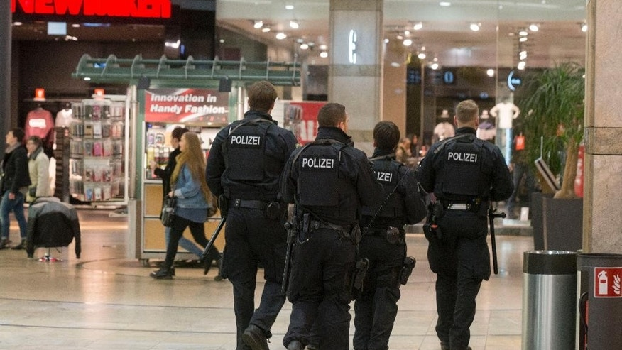 "In this Dec. 22, 2016 photo police units walk through the shopping centre ""Centro"" in Oberhausen, Germany. Two men were arrested in Duisburg on the suspicion of planning an attack on the shopping centre. (Arnulf Stoffl/dpa via AP)"