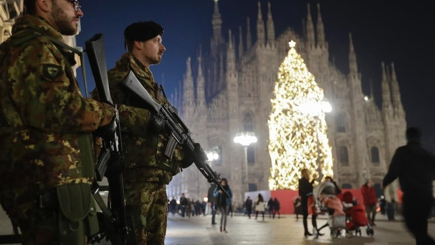 Italian soldiers patrol next to Milan's gothic cathedral, Italy, Thursday, Dec. 22, 2016. Following the truck attack on a Christmas market in Berlin, Italy is strengthening security measures for areas where crowds are expected for Christmas ceremonies. (AP Photo/Luca Bruno)