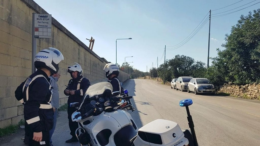 Maltese police officers close off a road by Malta's Luqa International airport after an Afriqiyah Airways plane from Libya landed at the airport in an apparent hijack, Friday, Dec. 23, 2016. Malta's state television says two hijackers who diverted a Libyan commercial plane to the Mediterranean island nation have threatened to blow it up. (AP Photo/Jonathan Borg)