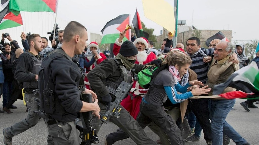 "Israeli border police officers scuffle with Palestinian protesters, some are dressed as Santa Claus, during a protest in front of an Israeli checkpoint, in the West Bank city of Bethlehem, Friday, Dec. 23, 2016. In a Christmas greeting on Friday, Palestinian President Mahmoud Abbas said: ""Despite the Israeli occupation, our presence in our homeland and the preservation of our cultural and national heritage are the most important form of resistance in the face of the darkness of a foreign colonialist occupying power."" (AP Photo/Nasser Nasser)"