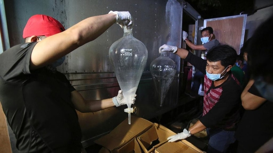 Members of the National Bureau of Investigation look at laboratory materials used to manufacture Methamphetamine, locally known as Shabu, that was seized from a truck that was parked inside a house of suspects in San Juan, east of Manila, Philippines on Friday, Dec. 23, 2016. Philippine authorities say they have arrested six people in what could be one of the largest drug seizures under President Rodrigo Duterte. (AP Photo/Aaron Favila)