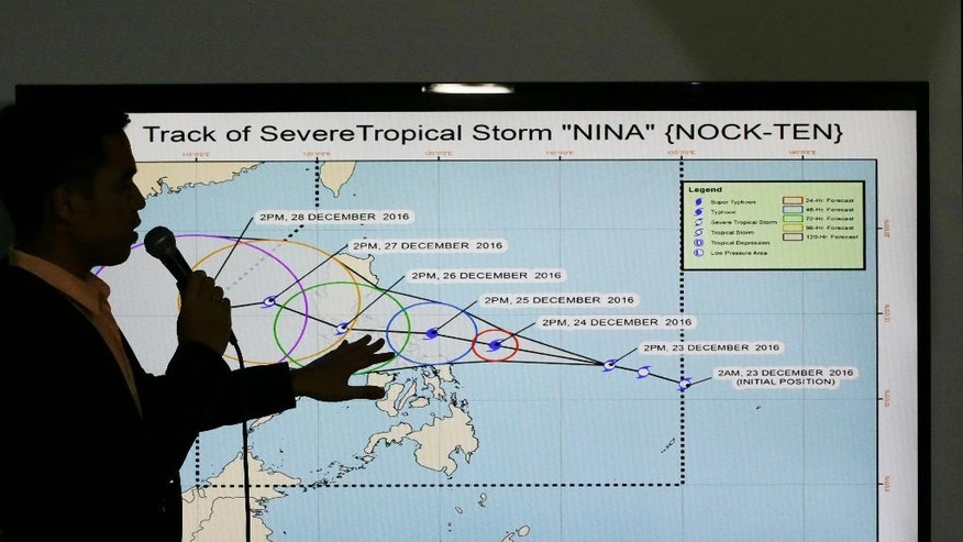 Filipino weather specialist Benison Estareja shows the track of Tropical Storm Nock-Ten during a press conference in Quezon city, north of Manila, Philippines on Friday, Dec. 23, 2016. A severe tropical storm has gained strength as it moves closer to the Philippines and may intensify further into a typhoon, bringing moderate to heavy rains and blustery weather on Christmas Day, the biggest holiday in the predominantly Roman Catholic nation, weather forecasters said. (AP Photo/Aaron Favila)