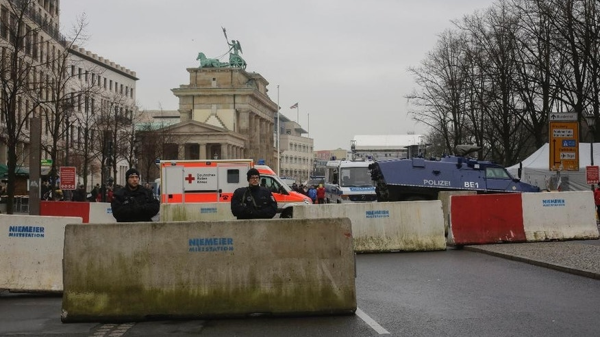 Armed police officers stand behind concrete blocks for protection near the Brandenburg Gate, background, in Berlin, Friday, Dec. 23, 2016, after Anis Amri, the suspect of the terrorist attack on a Christmas market in Berlin was shot in Milan, Italy. (AP Photo/Markus Schreiber)