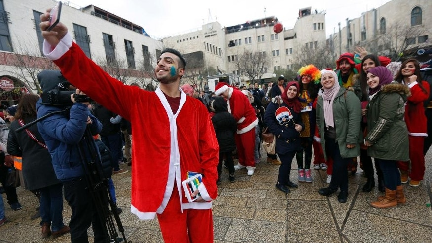 A Palestinian dressed as Santa Claus takes a picture on Christmas Eve in Manger Square, outside the Church of the Nativity, built atop the site where Christians believe Jesus Christ was born, in the West Bank City of Bethlehem, Saturday, Dec. 24, 2016. (AP Photo/Majdi Mohammed)