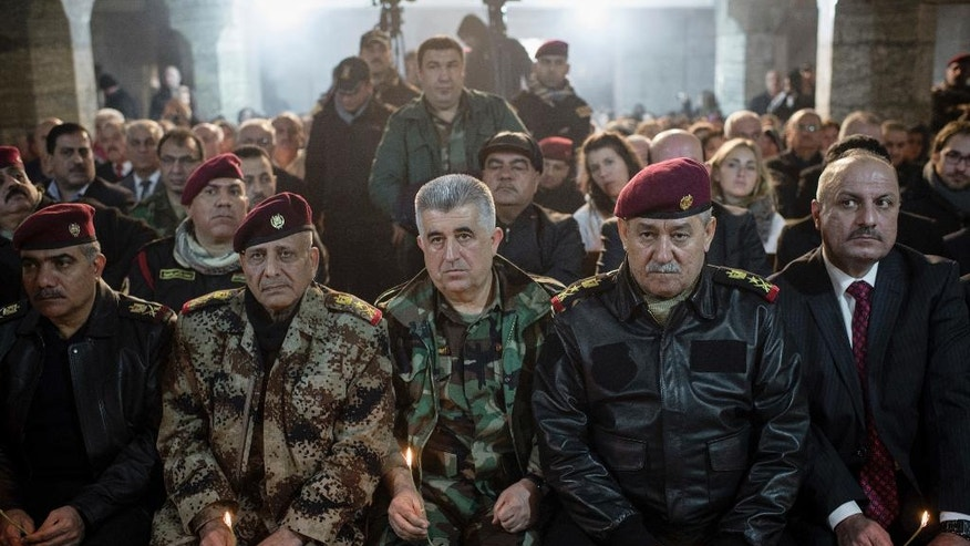 Iraqi Army and Peshmerga commanders attend Christmas Eve's Mass in the Assyrian Orthodox church of Mart Shmoni, in Bartella, Iraq, Saturday, December 24, 2016. For the 300 Christians who braved rain and wind to attend the mass in their hometown, the ceremony provided them with as much holiday cheer as grim reminders of the war still raging on around their northern Iraqi town and the distant prospect of moving back home. Displaced when the Islamic State seized their town in 2014, they were bused into the town from Irbil, capital of the self-ruled Kurdish region, where they have lived for more than two years. (AP Photo/Cengiz Yar)