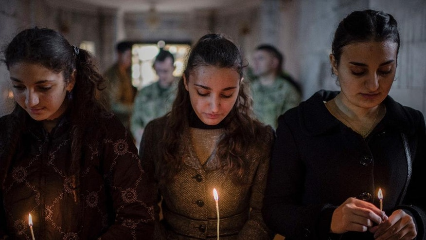 Iraqis attend Christmas Eve's Mass in the Assyrian Orthodox church of Mart Shmoni, in Bartella, Iraq, Saturday, December 24, 2016. For the 300 Christians who braved rain and wind to attend the mass in their hometown, the ceremony provided them with as much holiday cheer as grim reminders of the war still raging on around their northern Iraqi town and the distant prospect of moving back home. Displaced when the Islamic State seized their town in 2014, they were bused into the town from Irbil, capital of the self-ruled Kurdish region, where they have lived for more than two years. (AP Photo/Cengiz Yar)