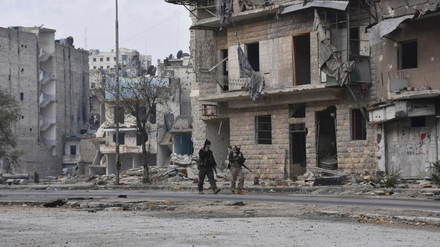 This photo released by the Syrian official news agency SANA shows Syrian army soldiers marching through the streets in the Ansari neighborhood, east Aleppo, Syria, Friday, Dec 23, 2016. Syrian rebels outside Aleppo on Friday shelled a neighborhood in the northern city, killing three people in the first bombardment since government forces took control of the whole city after opposition fighters in the eastern parts withdrew, state TV reported. (SANA via AP)