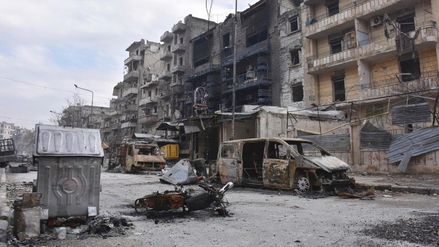 This photo released by the Syrian official news agency SANA, shows damaged buildings and cars in the Ansari neighborhood, east Aleppo, Syria, Friday, Dec 23, 2016. Syrian rebels outside Aleppo on Friday shelled a neighborhood in the northern city, killing three people in the first bombardment since government forces took control of the whole city after opposition fighters in the eastern parts withdrew, state TV reported. (SANA via AP)