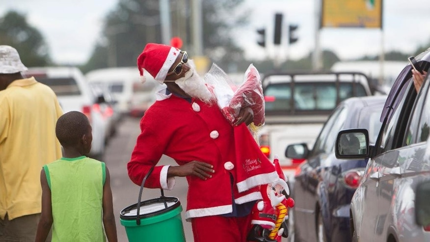 In this photo taken on Tuesday, Dec. 20, 2016, a motorist takes a picture of a man dressed as Santa Claus on the streets of Harare. Most people in this once-prosperous southern African country are struggling to afford Christmas as the economy implodes. (AP Photo/Tsvangirayi Mukwazhi)