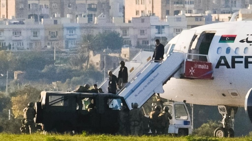 A man with a green flag is helped out an Afriqiyah Airways plane from Libya standing on the tarmac at Malta's Luqa International airport, Friday, Dec. 23, 2016. Two hijackers diverted a Libyan commercial plane to Malta on Friday and threatened to blow it up with hand grenades, Maltese authorities and state media said.  (AP Photo/Jonathan Borg)