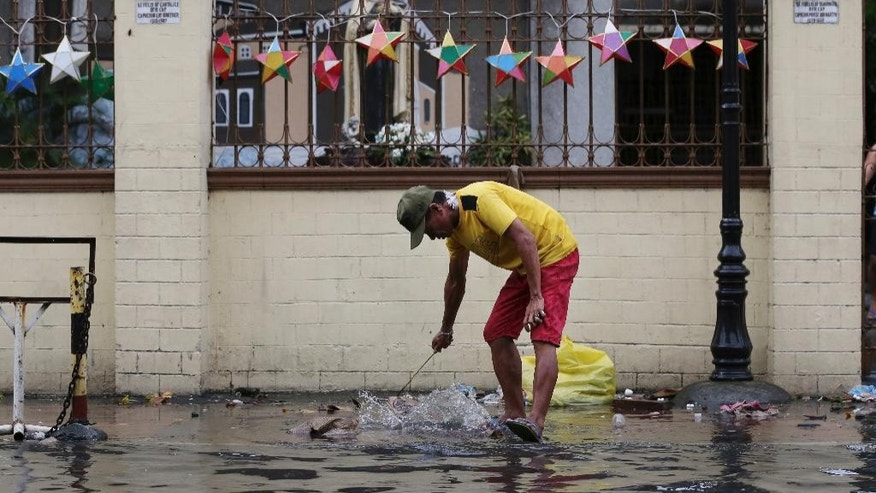A man cleans the trash along a flooded area outside a church caused by rains from Typhoon Nock-Ten in Quezon city, north of Manila, Philippines on Monday, Dec. 26, 2016. The powerful typhoon slammed into the eastern Philippines on Christmas Day, spoiling the biggest holiday in Asia's largest Catholic nation, where a governor offered roast pig to entice villagers to abandon family celebrations for emergency shelters. (AP Photo/Aaron Favila)