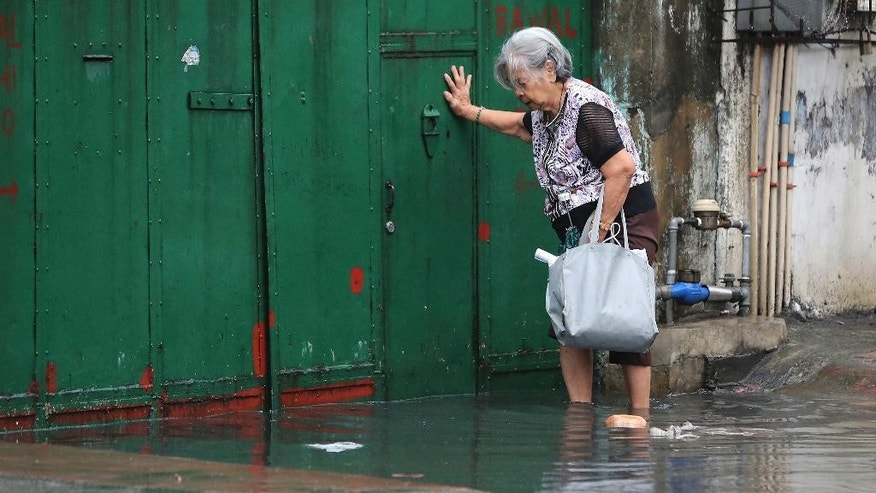 A Filipino woman crosses floodwaters caused by rains from Typhoon Nock-Ten in Quezon city, north of Manila, Philippines on Monday, Dec. 26, 2016. The powerful typhoon slammed into the eastern Philippines on Christmas Day, spoiling the biggest holiday in Asia's largest Catholic nation, where a governor offered roast pig to entice villagers to abandon family celebrations for emergency shelters. (AP Photo/Aaron Favila)