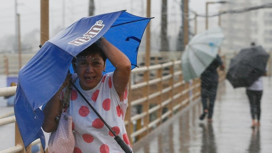 People brave the rain and wind brought about by typhoon Nock-Ten a day after Christmas Monday, Dec. 26, 2016 at suburban Paranaque city, southeast of Manila, Philippines. The powerful typhoon slammed into the eastern Philippines on Christmas Day, spoiling the biggest holiday in Asia's largest Catholic nation, where a governor offered roast pig to entice villagers to abandon family celebrations for emergency shelters. (AP Photo/Bullit Marquez)