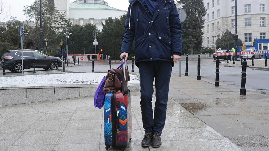Polish lawmaker Michal Stasinski poses in front of the parliament pulling a suitcase with warm clothes and carrying a bag filled with his mother's homemade cabbage-and-mushroom stuffed dumplings in Warsaw, Poland, Friday, Dec. 23, 2016. While most lawmakers were already home for Christmas, Stasinski was joining a group of opposition lawmakers hunkering down for sit-in occupation of parliament to protest what they consider backsliding on democracy by the populist government. (AP Photo/Alik Keplicz)