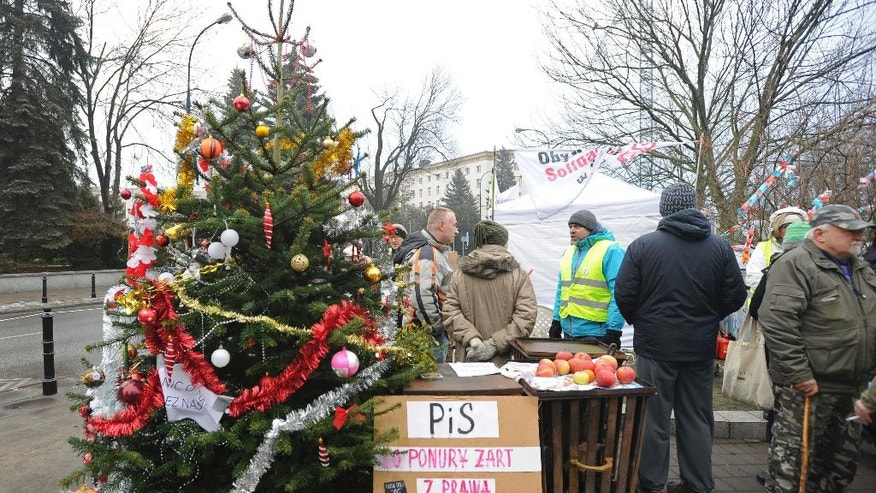 Protesters supporting opposition lawmakers stand next to a Christams Tree in front of the parliament in Warsaw, Poland, Friday, Dec. 23, 2016. While most lawmakers were already home for Christmas, opposition lawmakers hunkered down for sit-in occupation of parliament till the next session on Jan. 11, 2017, to protest what they consider backsliding on democracy by the populist government. (AP Photo/Alik Keplicz)