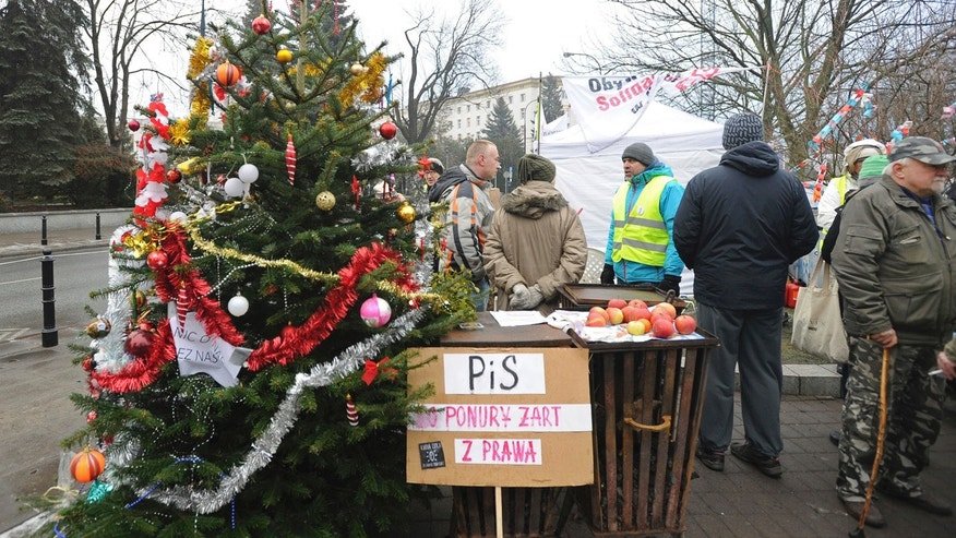 Protesters supporting opposition lawmakers stand next to a Christams Tree in front of the parliament in Warsaw, Poland, Friday, Dec. 23, 2016.