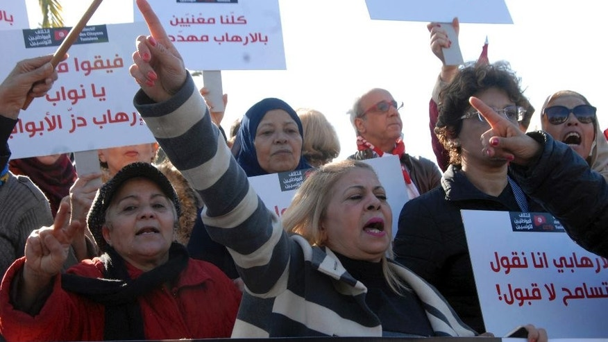People demonstrate outside the Tunisian parliament, in Tunis, Saturday, Dec. 24, 2016. About 200 people have protested in the Tunisian capital against the return of Tunisian jihadis who have fought abroad.The gathering was prompted by the deadly truck attack in a Berlin Christmas market by Tunisian Anis Amri, who had pledged allegiance to the Islamic State group and was killed Friday in a police shootout. Amri, 24, was slated to be deported home from Germany. (AP Photo)