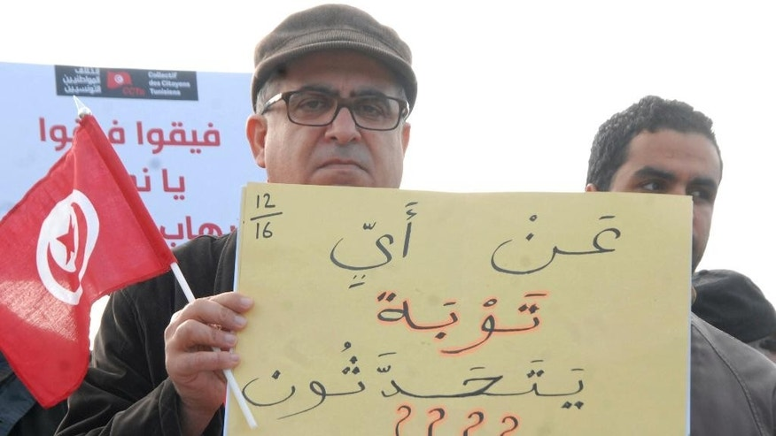 A man holds a poster reading 'What pardon are you talking about?' during a demonstration outside the Tunisian parliament, in Tunis, Saturday, Dec. 24, 2016. About 200 people have protested in the Tunisian capital against the return of Tunisian jihadis who have fought abroad.The gathering was prompted by the deadly truck attack in a Berlin Christmas market by Tunisian Anis Amri, who had pledged allegiance to the Islamic State group and was killed Friday in a police shootout. Amri, 24, was slated to be deported home from Germany. (AP Photo)