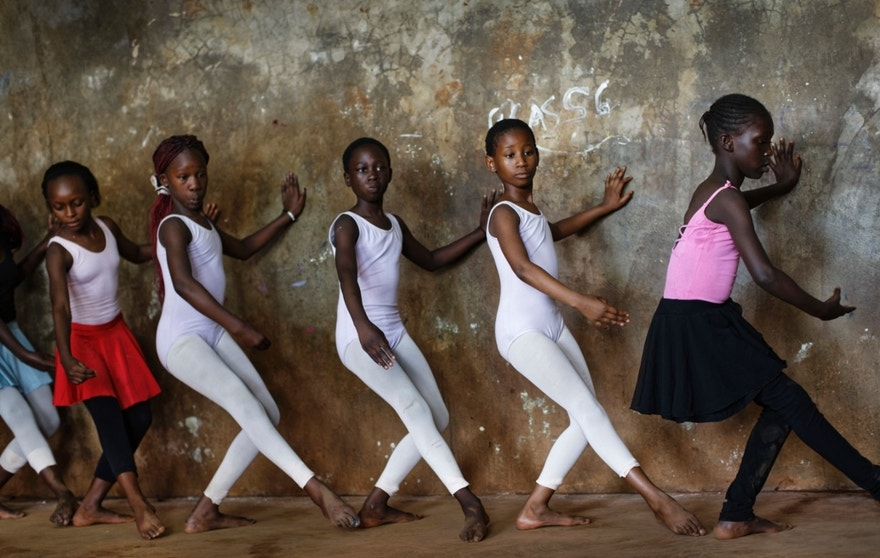 In this photo taken Friday, Dec. 9, 2016, young ballerinas practice under the instruction of Kenyan ballet dancer Joel Kioko, 16, in a room at a school in the Kibera slum of Nairobi, Kenya. In a country not usually associated with classical ballet, Kenya's most promising young ballet dancer Joel Kioko has come home for Christmas from his training in the United States, to dance a solo in The Nutcracker and teach holiday classes to aspiring dancers in Kibera, the Kenyan capital's largest slum. (AP Photo/Ben Curtis)