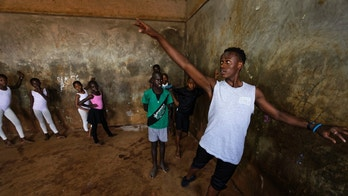 In this photo taken Friday, Dec. 9, 2016, young ballerinas receive instruction from Kenyan ballet dancer Joel Kioko, 16, right, in a room at a school in the Kibera slum of Nairobi, Kenya. In a country not usually associated with classical ballet, Kenya's most promising young ballet dancer Joel Kioko has come home for Christmas from his training in the United States, to dance a solo in The Nutcracker and teach holiday classes to aspiring dancers in Kibera, the Kenyan capital's largest slum. (AP Photo/Ben Curtis)