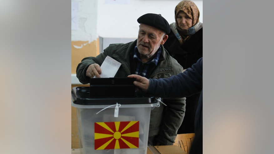 An ethnic Albanian couple vote at a polling station in village of Tearce, in northwestern Macedonia, on Sunday, Dec. 25, 2016. Authorities in Macedonia have ordered a Christmas Day rerun of a parliamentary election in one voting district - a decision that could threaten the slim majority of the long-governing conservatives. (AP Photo/Boris Grdanoski)