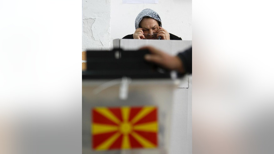 A woman puts on her glasses before voting at a polling station in village of Tearce, in northwestern Macedonia, on Sunday, Dec. 25, 2016. Authorities in Macedonia have ordered a Christmas Day rerun of a parliamentary election in one voting district - a decision that could threaten the slim majority of the long-governing conservatives. (AP Photo/Boris Grdanoski)