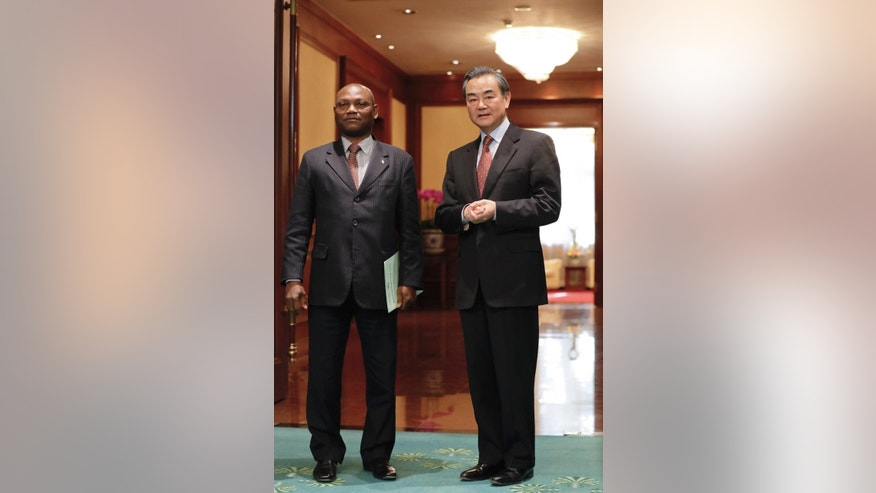 Chinese Foreign Minister Wang Yi, right, stands with his Sao Tome counterpart Urbino Botelho after a signing ceremony at the Diaoyutai State Guesthouse in Beijing, Monday, Dec. 26, 2016. China and Sao Tome and Principe officially resumed diplomatic relations on Monday, in a triumph for Beijing over rival Taiwan after the African island nation abruptly broke away from the self-ruled island last week. (AP Photo/Andy Wong)