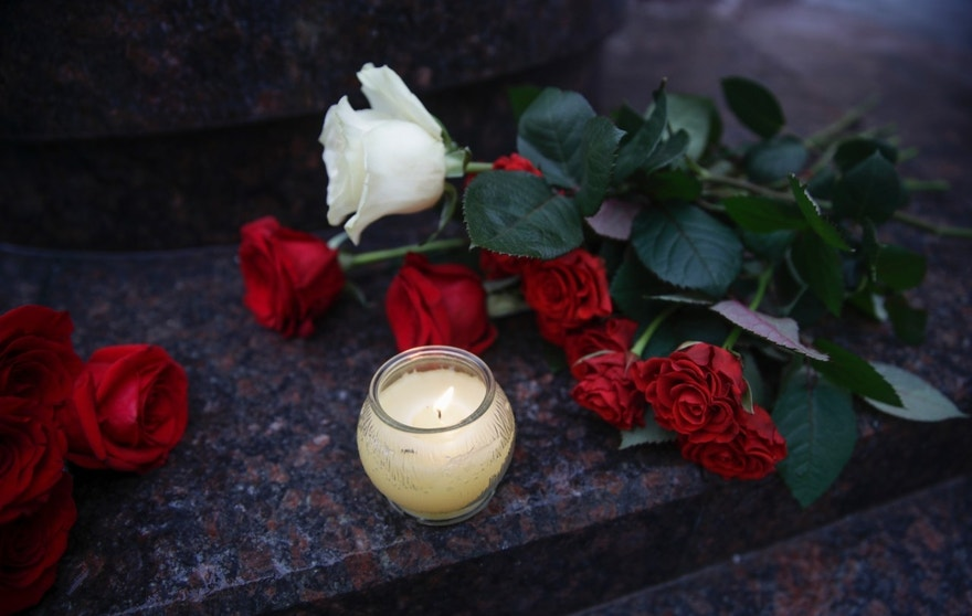 Flowers and candles are placed at the well-known military choir's building in Moscow, Russia, Sunday, Dec. 25, 2016, after a plane carrying 64 members of the Alexandrov Ensemble, crashed into the Black Sea minutes after taking off from the resort city of Sochi. The Russian plane was headed for an air base in Syria with 92 people aboard, Russia's Defense Ministry said. (AP Photo/Pavel Golovkin)