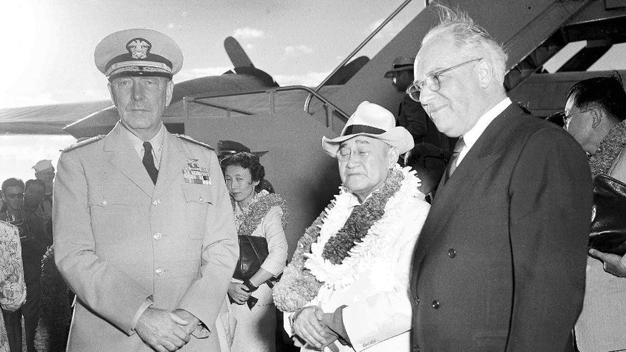 FILE - In this Aug. 31, 1951, file photo, Japanese Prime Minister Shigeru Yoshida, center right, accompanied by his daughter, Kazuko, center left, is greeted by Adm. Arthur Radford, left, commander of the U.S. Pacific Fleet, and Joseph R. Farrington, who serves as a delegate of the U.S. Congress for the Territory of Hawaii, during an arrival ceremony for Yoshida in Honolulu, Hawaii. Yoshida is best remembered for signing the San Francisco peace treaty with the U.S. and others in 1951, allowing Japan back into international society after its war defeat. His Pearl Harbor visit, which he made on his way home from San Francisco, was largely eclipsed by the historic treaty. (AP Photo/File)