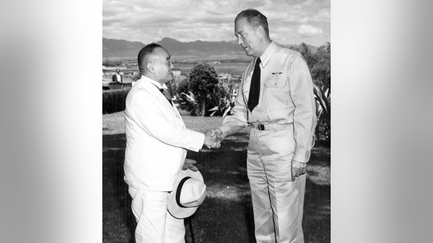 In this Sept. 12, 1951 photo provided by the U.S. Navy, Japanese Prime Minister Shigeru Yoshida, left, shakes hands with Adm. Arthur Radford, commander of the U.S. Pacific Fleet, at Radford's headquarters overlooking Pearl Harbor in Hawaii. Yoshida made the stop in Hawaii as he was traveling back to Japan from the San Francisco conference that restored Japan's sovereignty. Yoshida is best remembered for signing the San Francisco peace treaty with the U.S. and others in 1951, allowing Japan back into international society after its war defeat. His Pearl Harbor visit, which he made on his way home from San Francisco, was largely eclipsed by the historic treaty. (U.S. Navy via AP)