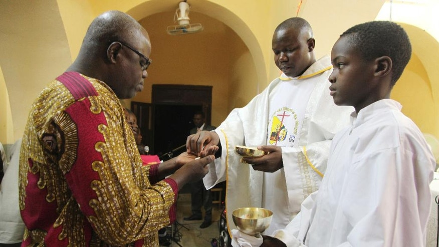 In this photo taken Saturday, Dec. 24, 2016, Anthero Afeku, a Catholic priest , centre, performs a communion mass to celebrate Christmas at Philippe Amore Catholic Church in Goa, Mali. Just four years ago strict Islamic law was in force in this town, but Christians have returned to rebuild their congregation that fled the jihadist occupation. (AP Photo/Baba Ahmed)
