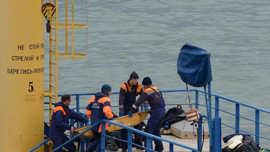 Russian rescue workers attend the scene of the crashed plane at a pier just outside Sochi, Russia, Sunday, Dec. 25, 2016. Russian ships, helicopters and drones are searching for bodies after a plane carrying 92 people crashed into the Black Sea. The plane was taking the Alexandrov Ensemble, a military choir, to perform at Russia's air base in Syria when it went down shortly after takeoff. (AP Photo/Viktor Klyushin)
