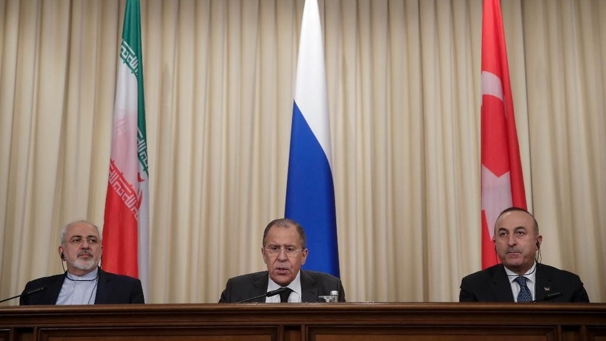 FILE -- In this Tuesday, Dec. 20, 2016 file photo, Iranian Foreign Minister Mohammad Javad Zarif, left, Russian Foreign Minister Sergey Lavrov, center, and Turkey's Foreign Minister Mevlut Cavusoglu, attend a joint news conference after their talks in Moscow, Russia. With his victory in Aleppo, Syrian President Bashar Assad appears to have survived a nearly six-year war to drive him from power, but he is now more dependent on outside powers than ever. His key allies Russia and Iran, along with Turkey, are best placed to determine Syria's endgame, which could more closely resemble a grand bargain among great powers than a political settlement among Syrians themselves. (AP Photo/Pavel Golovkin, File)