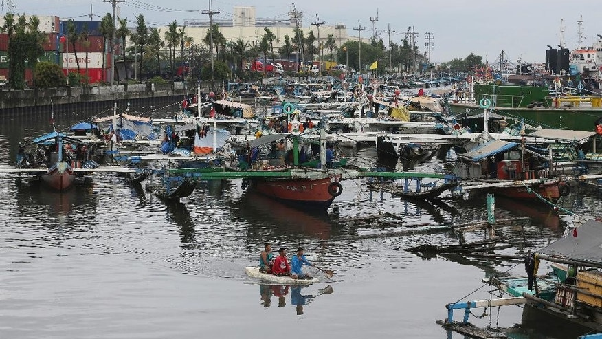 Filipinos riding an improvised float pass by fishing boats that took shelter from Typhoon Nock-Ten in Manila, Philippines Monday, Dec. 26, 2016. The powerful typhoon slammed into the eastern Philippines on Christmas Day, spoiling the biggest holiday in Asia's largest Catholic nation, where a governor offered roast pig to entice villagers to abandon family celebrations for emergency shelters. (AP Photo/Aaron Favila)
