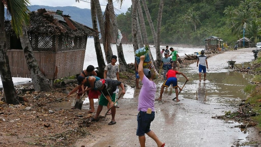 Residents clean the road a day after typhoon Nock-Ten hit Mabini township, Batangas province south of Manila, Philippines on Monday, Dec. 26, 2016. The powerful typhoon slammed into the eastern Philippines on Christmas Day, spoiling the biggest holiday in Asia's largest Catholic nation but weakened slightly on Monday as it roared toward a congested region near the country's capital, officials said. They said that Typhoon Nock-Ten had cut power to five provinces as well as displacing thousands of villagers and travelers in Asia's Catholic bastion.(AP Photo/Bullit Marquez)