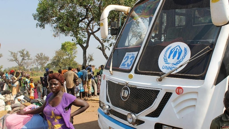 In this Sunday, Dec. 11, 2016 photo, a women stands in front of a UNHCR passenger bus next to a refugee registration site near Bibi bidi, Uganda. About 440,000 people have fled South Sudan's spiraling civil war into Uganda this year alone, creating refugee settlements that have become some of the world's largest in just six months. Many local Ugandans who were once refugees themselves see the newcomers as welcome. (AP Photo/Justin Lynch)